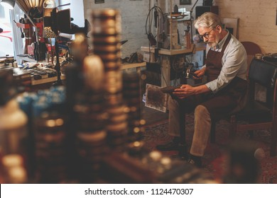 An elderly shoemaker at work in a workshop