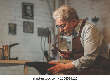 An elderly shoemaker at work in the workshop