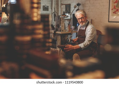 An elderly shoemaker working in a studio