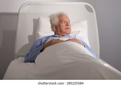 Elderly sick male patient lying in hospital bed