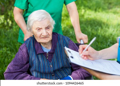 Elderly sick woman in wheelchair, medical nurses discussing treatment outdoor
