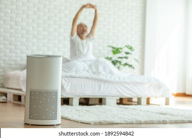 Elderly sleep with Air purifier in cozy white bed room for filter and cleaning removing dust PM2.5 HEPA in home,for fresh air and healthy life,Air Pollution Concept