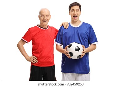 Elderly soccer player and a young soccer player with a football looking at the camera isolated on white background