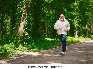Elderly sporty man running in green forest during morning workout, copy space. Healthy and active lifestyle at any age concept