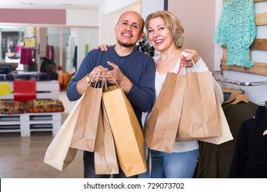 elderly spouses carrying bags with purchases in clothing store