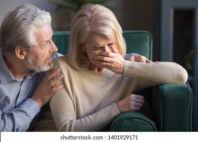 Elderly spouses sit on sofa at home, desperate wife crying worried anxious husband embrace her comforting beloved woman, sad life event, senile disease diagnosis, psychological mental problems concept