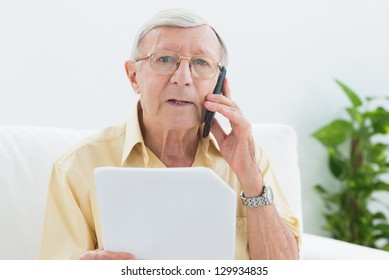 Elderly stern man reading papers on the phone on a sofa