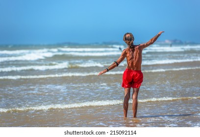 An elderly swimmer standing in the waves of the sea with his arms spread around
