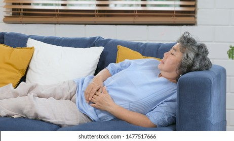 Elderly take a nap, Senior asian woman sleeping on sofa, Asia female napping at home living room in day, Old, retirement people lying  on sofa to take some rest