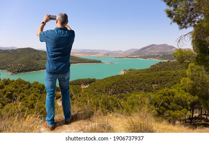 An elderly tourist stands at a viewpoint in the mountains of Andalusia near Marbella and takes a landscape photo with his smartphone. Below is the large Guadalteba reservoir.