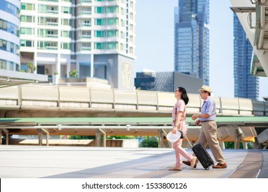 Elderly tourists, men and women, are walking dragging luggage. There is a building in the background during the daytime. Vacation travel concept