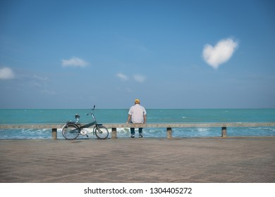 An elderly unrecognizable man in yellow cap is siting on the seashore, looking to heart clud on sky.