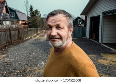 Elderly village man outdoors near the house