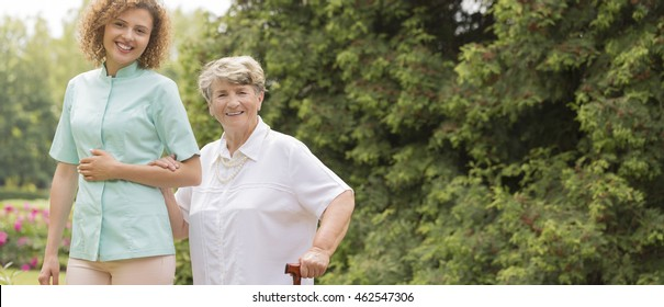 Elderly with walking stick and female caregiver outdoor