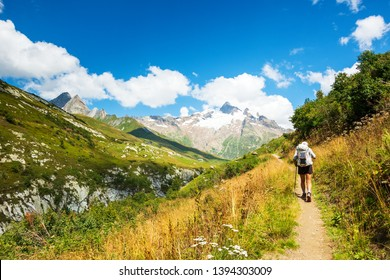 Elderly wellness. Senior man hiking French Alps in summer with solar backpack. The Aiguille des Glaciers, mountain in the Mont Blanc massif. View From Chapieux valley, Savoie, France.