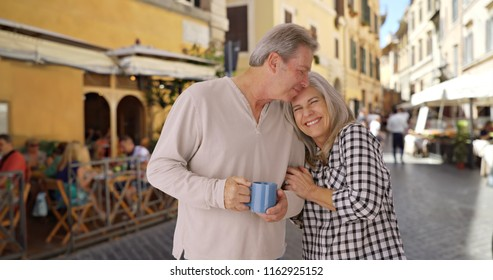 Elderly white couple in love embrace each other outside cafe in Rome