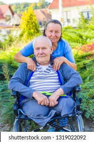 Elderly wife supporting her crippled husband in wheelchair outdoors.