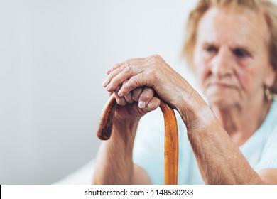 Elderly woman in the 80s with a walking stick