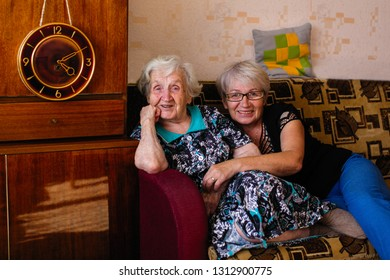 Elderly woman with adult daughter posing for photo in his home .