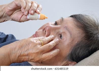 elderly woman applying eye drops on bed