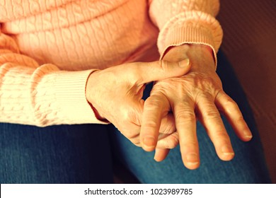 Elderly woman applying moisturizing lotion cream on hand palm, easing aches. Senior old lady experiencing severe arthritis rheumatics pains, massaging, warming up arm. Close up, copy space, background