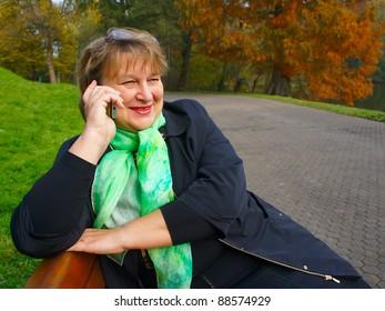 An elderly woman in  autumn park  talking on the phone
