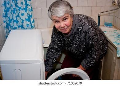 elderly woman in a bathroom near a washing-machine