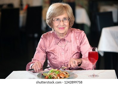 An elderly woman, a beautiful grandmother in a restaurant drinking Morse. Healthy lifestyle. Worthy old age. Beautiful old age and longevity. The concept of longevity and health.