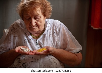 Elderly woman with beautiful wrinkled face is holding medicine pills in her hands to wash down  medication.