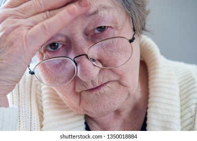 Elderly woman with beautiful wrinkled face is holding pills in her hands to choose medicines. Selective focus depth of field
