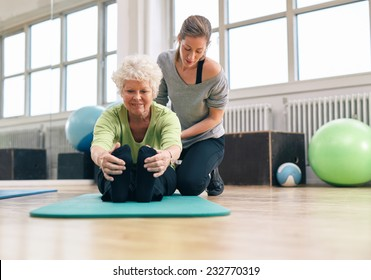 Elderly woman being helped by her instructor in the gym for exercising. Senior woman sitting on fitness mat bending forward and touching her toes with her personal trainer assisting.