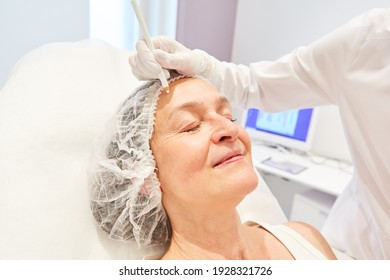 Elderly woman is being prepared for a facelift with a dermal filler made from hyaluronic acid at the dermatologist