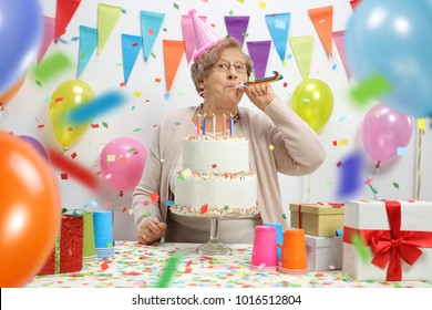 Elderly woman with a birthday cake blowing a party horn against a wall with balloons and decoration flags