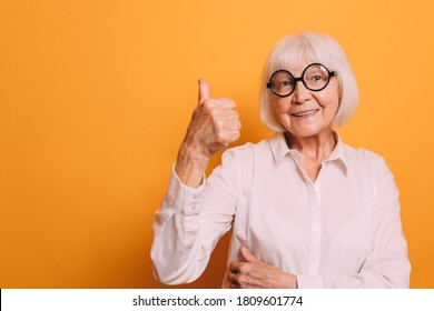 Elderly woman with blond hair in round glasses wearing white shirt, red pants and leopard print belt, thumbing up and smiling. Woman isolated over orange background