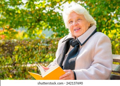 elderly woman with a book resting on a bench