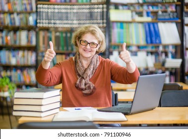 Elderly woman with books and laptop in library showing thumbs up