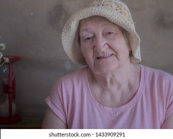 Elderly woman with bouquet of medical daisies in pink T-shirt and hat. Pensioner engaged in procurement of medicinal herbs and flowers for pharmacies. Alternative medicine. Village witch doctor, quack
