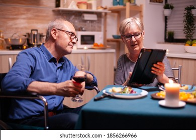 Elderly woman browsing on tablet pc and disabled husband in wheelchair holding wine glass. Imobilized handicapped senior husband browsing on phone enjoying the festive male, drinking a glass of red