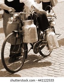 elderly woman carrying milk cans with a old rusty bicycle