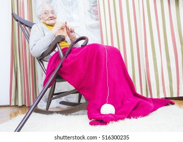 Elderly woman in chair doing relaxing hobby - knitting.