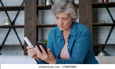 Elderly woman checks the recipe using her smartphone. Holds a smartphone in one hand and pill in the other
