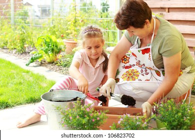 Elderly woman and child replanting flowers for better growth