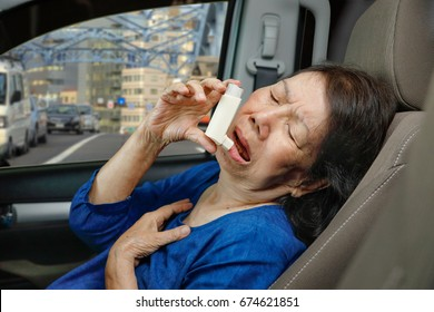 Elderly woman choking and holding an asthma spray inside car on