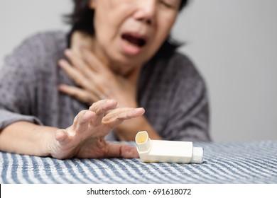 Elderly woman choking and holding an asthma spray