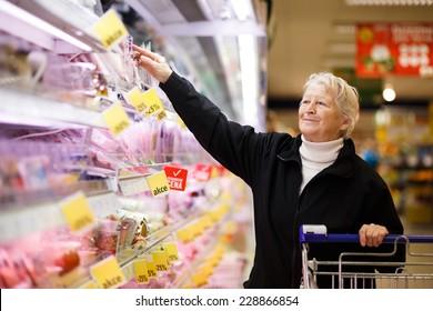 Ältere Frau, die Milcherzeugnisse im Supermarkt auswählt, im Laden für Milchprodukte im Lebensmittelgeschäft/Supermarkt einkaufen ( farbiges Bild )