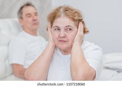 The elderly woman closed her ears with her hands, so as not to hear the deceit of her husband
