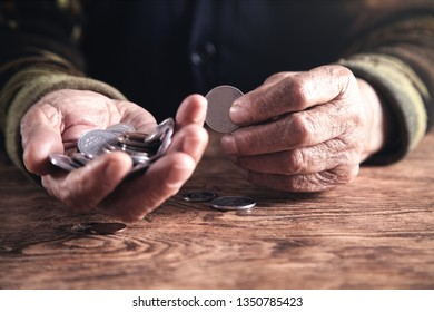 Elderly woman counting money on wooden table.