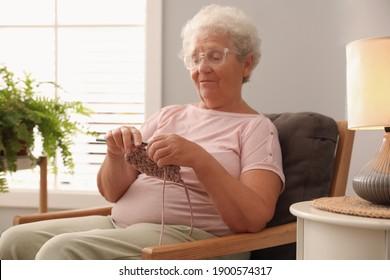 Elderly woman crocheting at home. Creative hobby