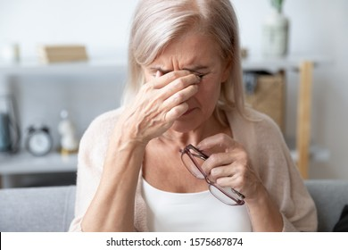 Elderly woman crying wipes tears with hands feels unhappy, bad news. Middle-aged woman taking off glasses closed eyes rubbing eyelid suffers from eye strain deterioration eyesight with age concept