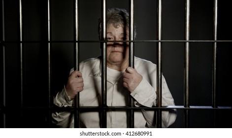 Elderly woman in Dark Prison behind bars of the jail
